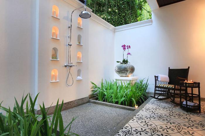 grüne kleine pflanzen im garten mit stühlen und tisch aus holz und mit kleinen kerzen, viele kerzen und eine gartendusche