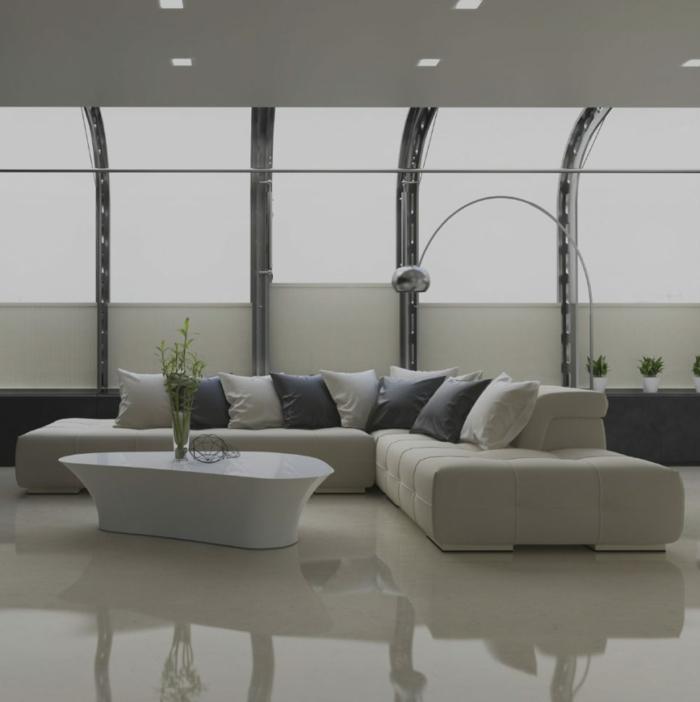 Betonboden Wohnbereich, blaue und weiße Kissen, ein weißer Tisch, Deckenleuchten