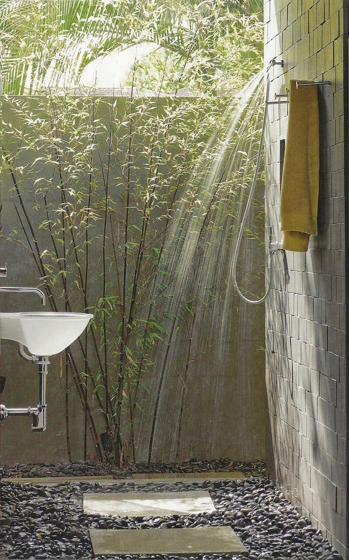 gartenweg und boden aus fliesen und grauen steinen, garten mit einem weißen waschbecken, eine graue wand und eine dusche
