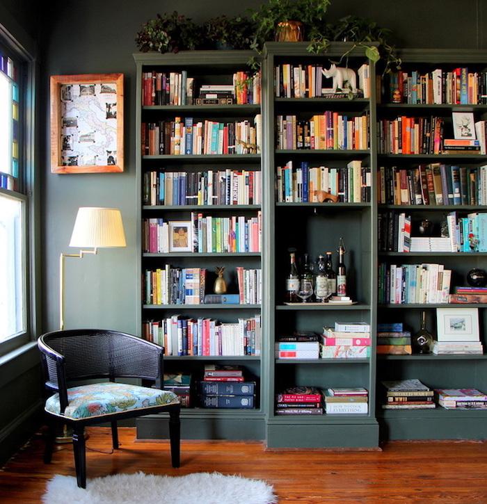 bücherregale im zimmer, viele bücher zuhause, schönes design von einem sessel, bunte farben wohnzimmer einrichten