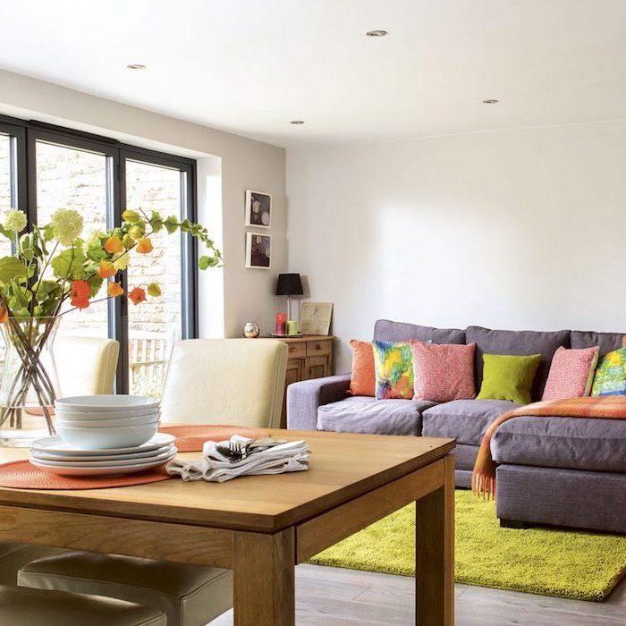 wohnzimmerwand ideen, graues sofa mit bunten kissen, großer tisch quadratisch