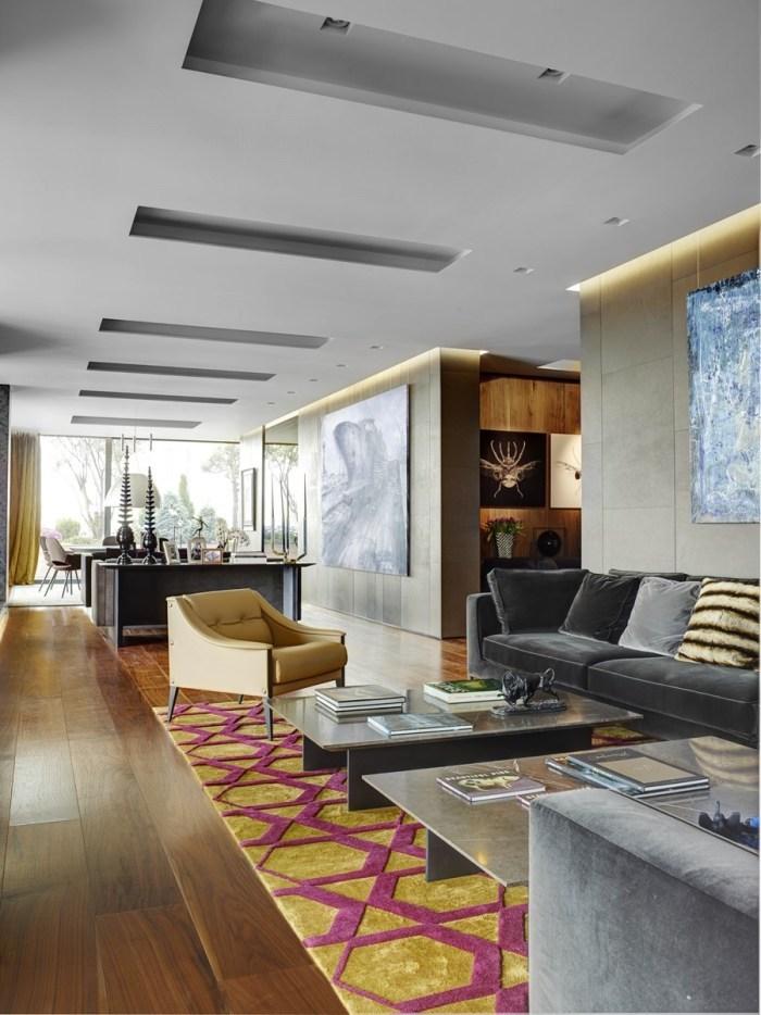 farbenfrohe wohnideen wohnzimmer, teppich in besonderen farben gelb und zyklame, dunkelgraues sofa, holzdeko, sessel in gelb
