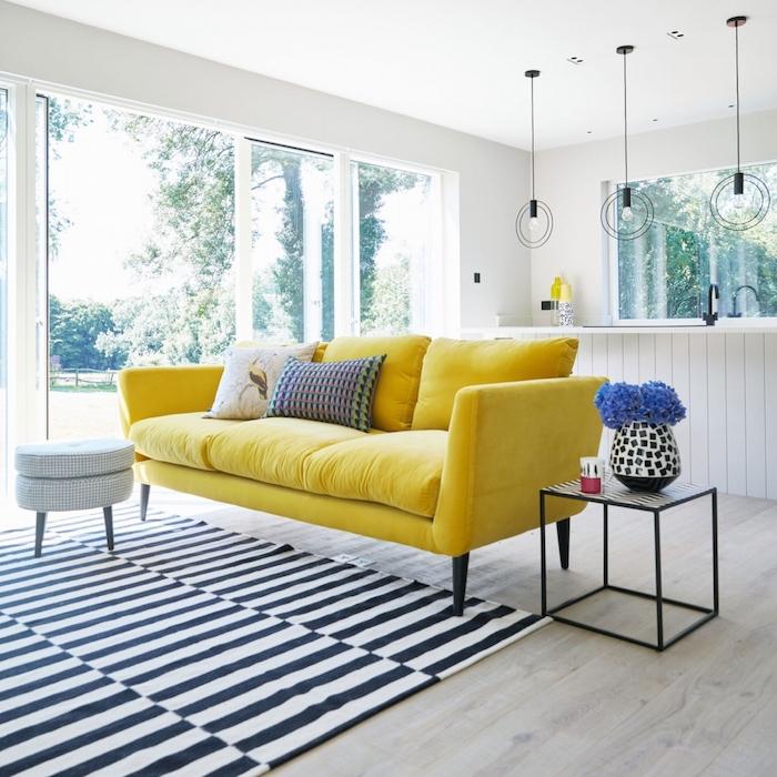 wohnzimmer wandfarbe, gelbes sofa, gestreifter teppich, runde hängelampen, blaue blumen
