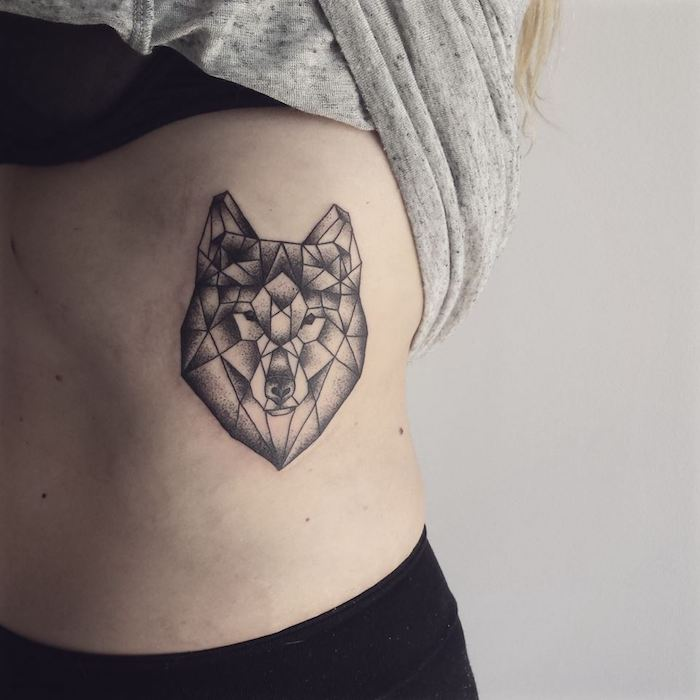 kleines schwarzes tattoo mit einem wolf mit schwarzen augen und einer schwarzen nase und mit vielen schwarzen geometrischen formen, eine frau mit einem wolf tattoo