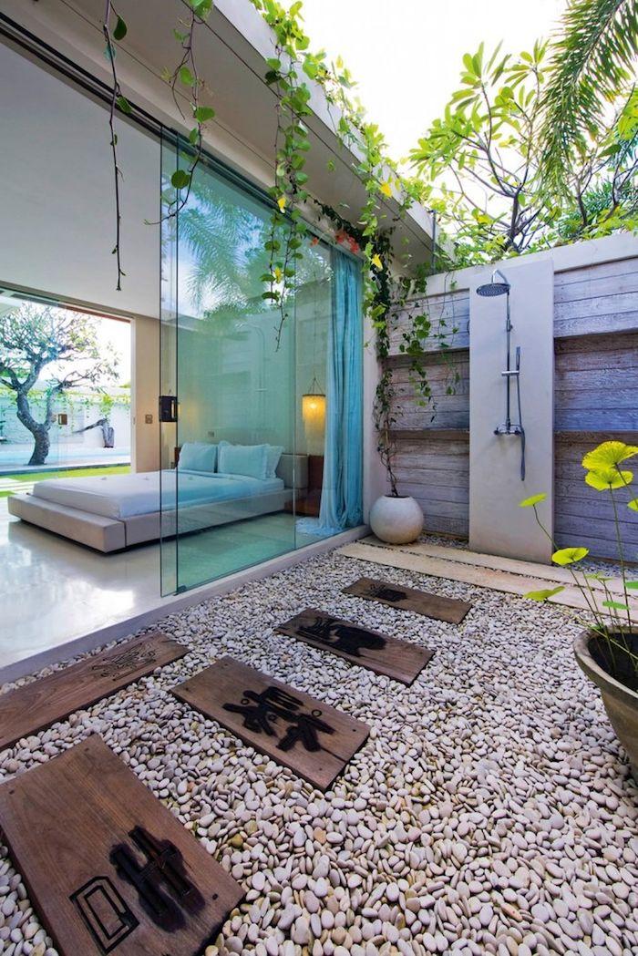 blumentopf mit gelben blumen unf grünen blätternl boden aus grauen steinen, wohnzimmer mit weißen bett und weißen kissen