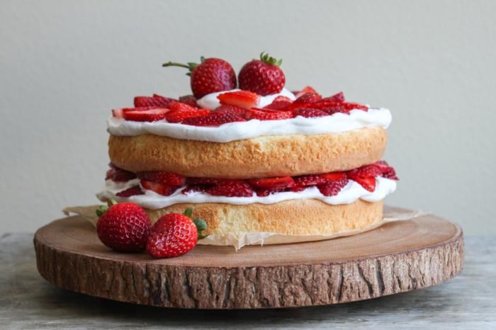 ein Kuchen mit weißer Creme und Erdbeeren als Dekoration, auf Holzplatte