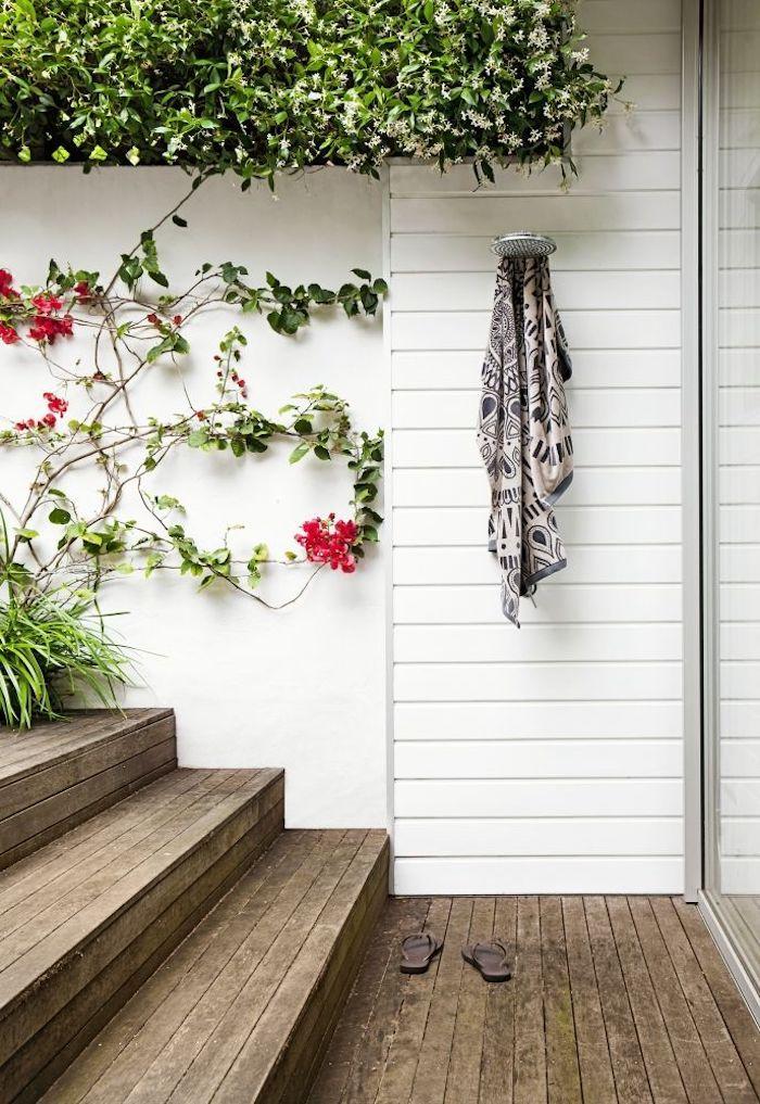 zwei brauen badelatschen und braune treppen aus holz, garten mit grünen pflanzen und roten blzmen und einer gartendusche