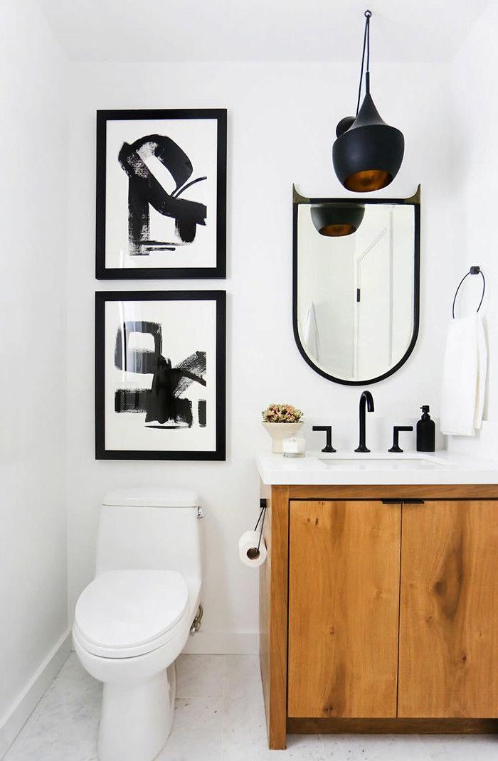 zwei Bilder mit schwarzen Figuren, ein Spiegel mit ausgefallener Form, Badmöbel Set aus Holz, schwarze Lampe, Badezimmer einrichten