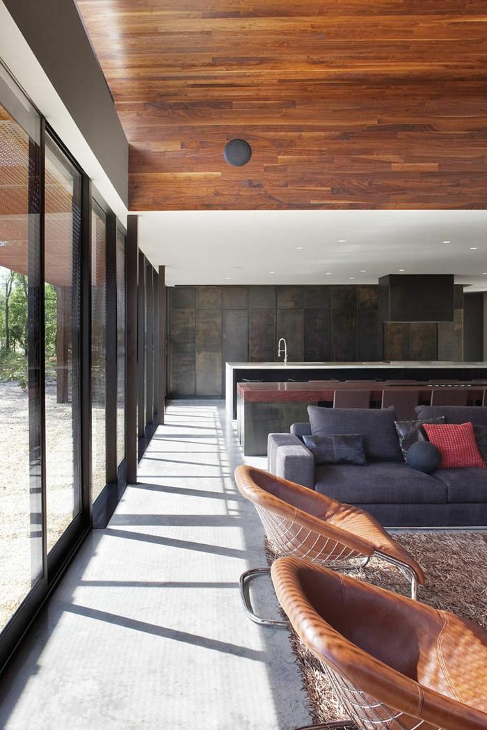 Betonboden Wohnbereich, eine Einzimmerwohnung, Wohnzimmer mit grauem Sofa, eine Kochinsel