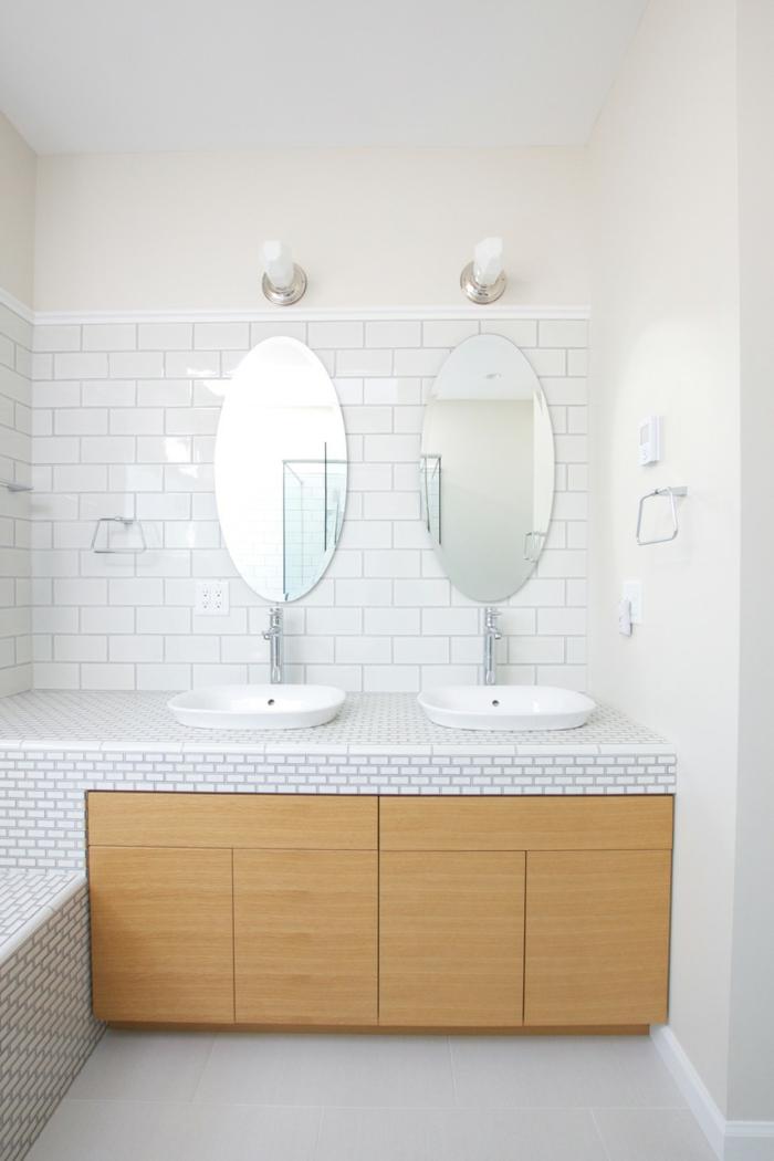 zwei Spiegel mit Waschbecken, Unterschränke aus Holz, weiße Fliesen an der Wand, Badezimmer einrichten