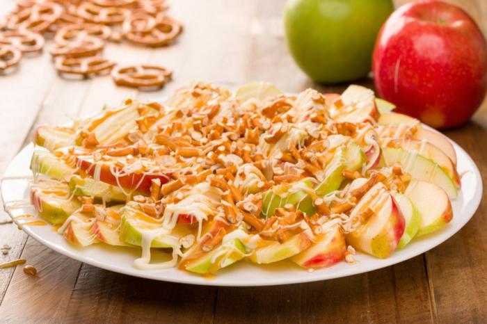 Äpfel, Brezelstangen, Karamell, Halloween Snacks, weiße Creme, alles aufeinander in einem Teller