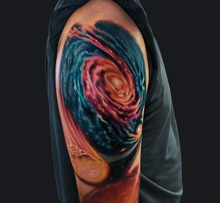 tätowierung mit glaxie als motiv, amazing tattoos für männer, oberarm