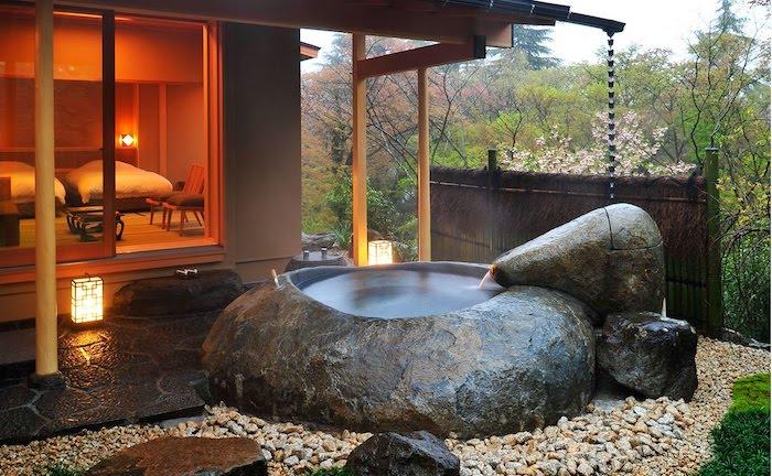 große graue steine und eine badewanne, ein haus mit kleinem garten mit einem boden aus vielen weißen steinen