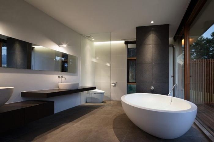 badezimmer einrcihtung in weiß und anthrazit, trennwand aus glas, ovale badewanne, modern