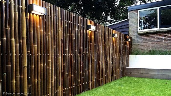 ein zaun mit braunen langen bambus stäben, ein sichtschutz zaun aus holz, ein garten mit einem grünen rasen, sichtschutz selber bauen ideen