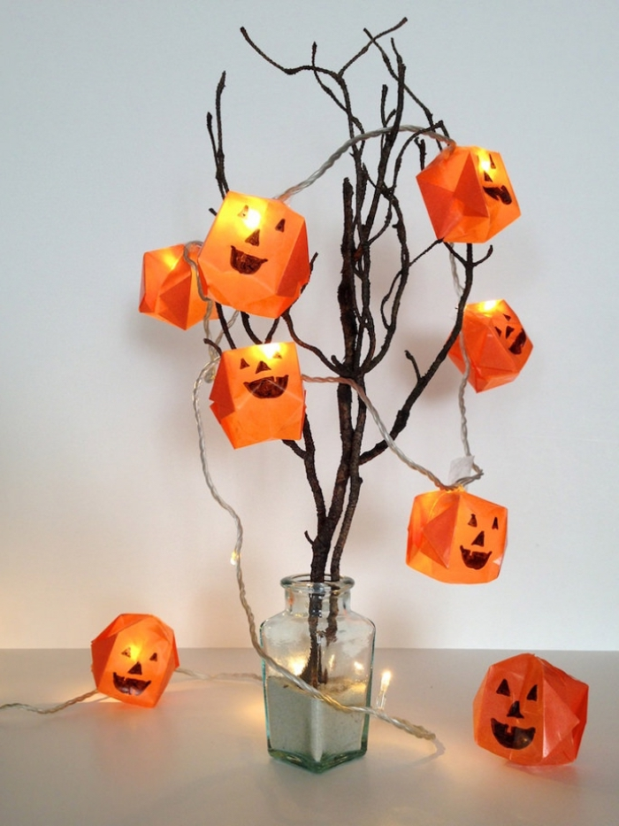 bastelideen halloween, glasvase mit sand, lichterkette dekoriert mit origami kürbissen, zweige