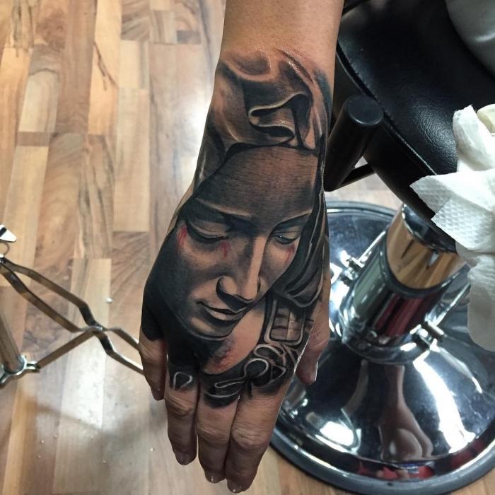 beste tattoos der welt, weinende frau am handgelenk, realitische tätowierung i schwazr und grau, frauengesicht