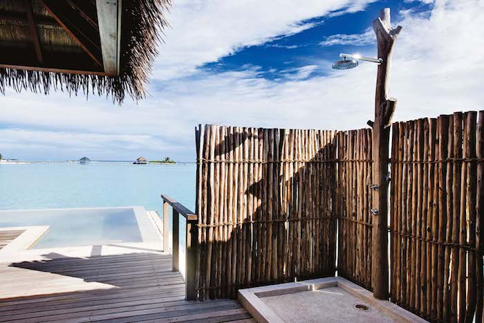 meer und ein blauer himmel mit vielen weißen wolken, ein haus mit terrasse mit einer kleinen outdoor dusche holz