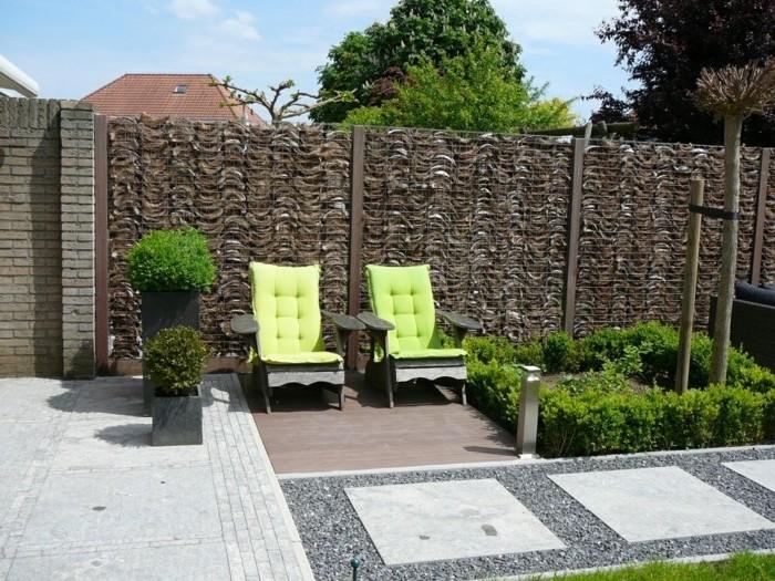 zwei kleine liegestrühle mitr grünen kissen und ein garten mit einem braunen zaun aus großen braunen gabionenwänden mit natursteinen, sichtschutz selber bauen ideen und eine grüne hecke