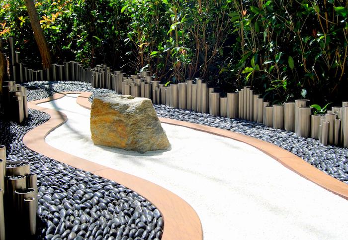 weißer gartengeg mit vielen kleinen grauen natursteinen, sichtschutz selber bauen mit grünen pföanzen mit grünen blättern, gartengestaltung bilder mit steingarten