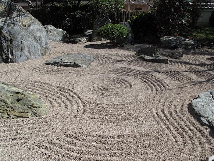 viele große graue steine und boden aus kleinen steinen und mit grünen kleinen pflanzen, steingarten deko ideen diy