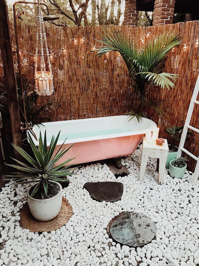 sichtschutz gartendusche aus holz, eine kleine pinke badewanne und ein boden aus vielen kleinen weißen steinen, blumentöpfe mit grünen pflanzen und grünen blättern und eine gartendusche