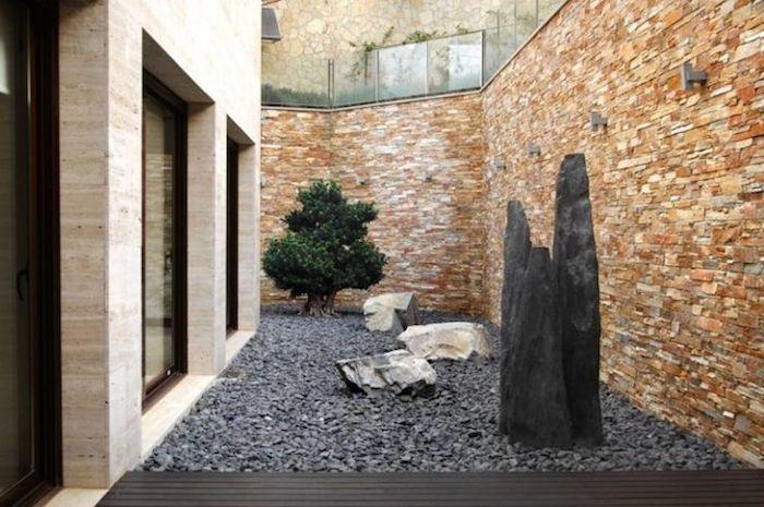 haus mit braunen fenstern und ein garten mit vielen kleinen grauen steinen, großer schwarzer stein und ein baum mit grünen blättern, ein zaun mit beigen steinen