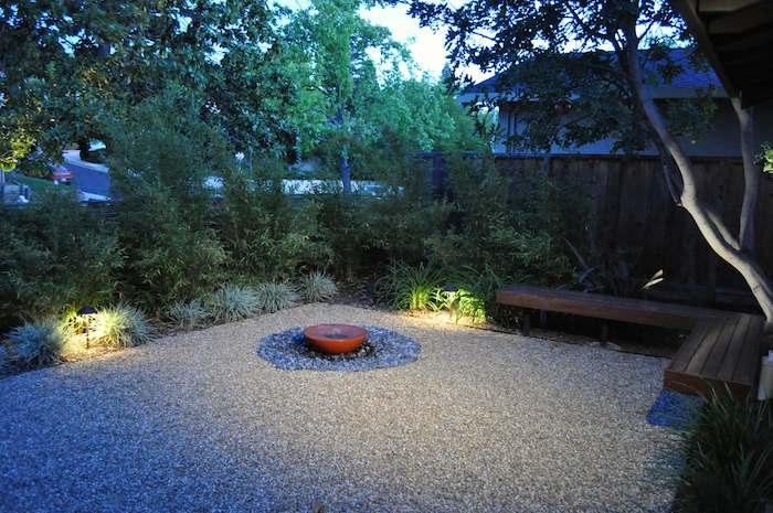kleine bank aus holz im garten mit boden mit vielen kleinen grauen steinen, einen garten sichtschutz selber bauen, sichtschutz aus vielen grünen pflanzen