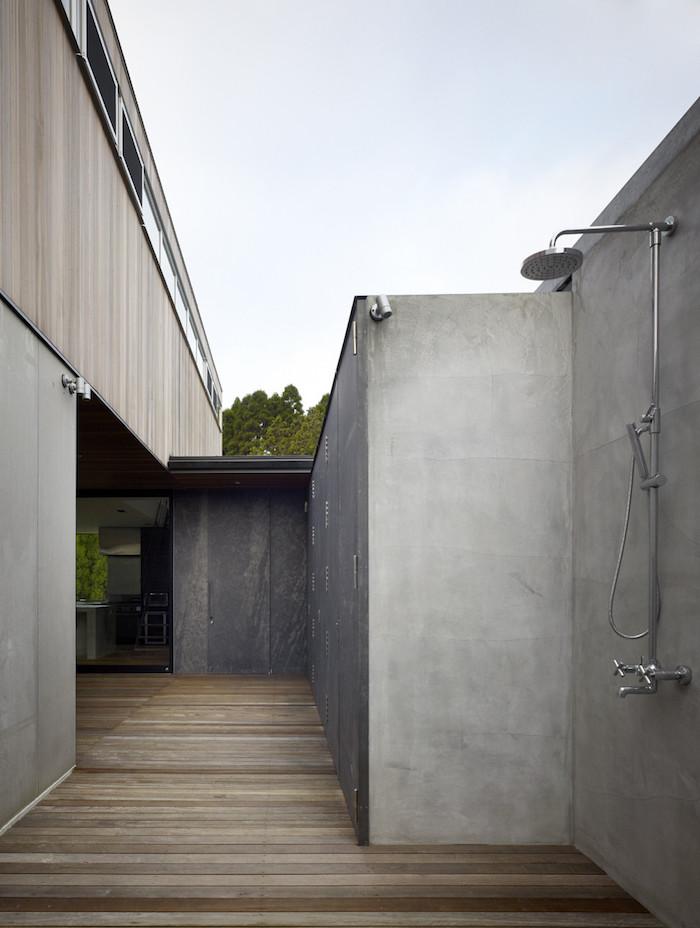 gartengestaltung ideen diy, ein haus mit einer grauen terrasse mit braunem boden aus holz und einem grauen sichtschutz, eine gartendusche edelstahl