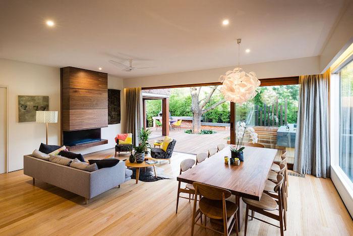 wohnzimmer mit einem braunen tisch aus holz und braunen stühlen, sofa mit weißen und schwarzen kissen, garten mit einem sichtschutz aus sichtschutz pflanzen und mit boden aus holz