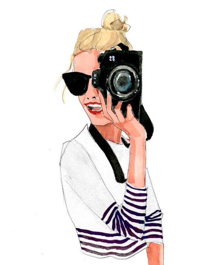 Frau mit Kamera und Sonnenbrille, weiße Bluse mit gestreiften Ärmeln, blonde Haare, roter Lippenstift