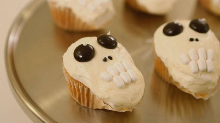 einige Schädel auf Cupcakes mit Creme, Bonbons als Dekoration, Halloween Snacks