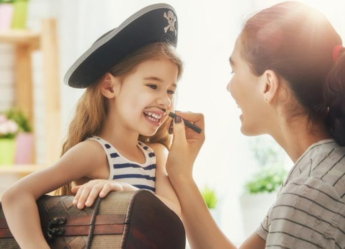 ein Mädchen spielt mit Ihrer Mutter, Mädchen Piratenkostüm, ein Spielzeug Schatzkiste, Halloween Verkleidung