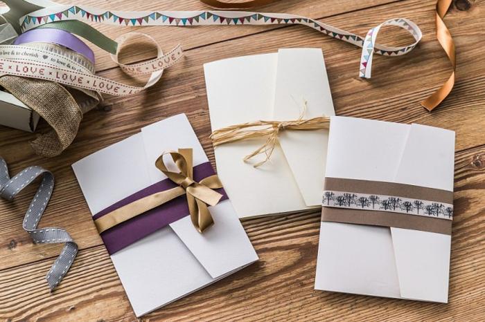 weiße Briefumschläge mit bunten Bändern und andere kreative Elemente, Hochzeitsdeko