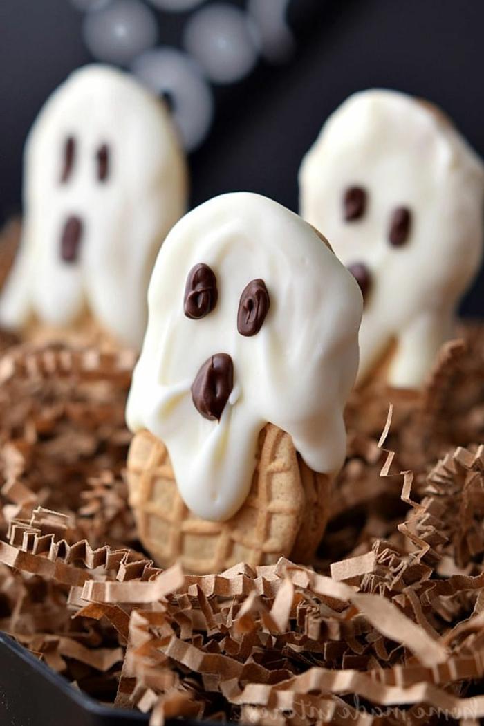 Gespenster mit weißer Creme und Schokoladen Augen und Mund, auf Kekse, Halloween Snacks