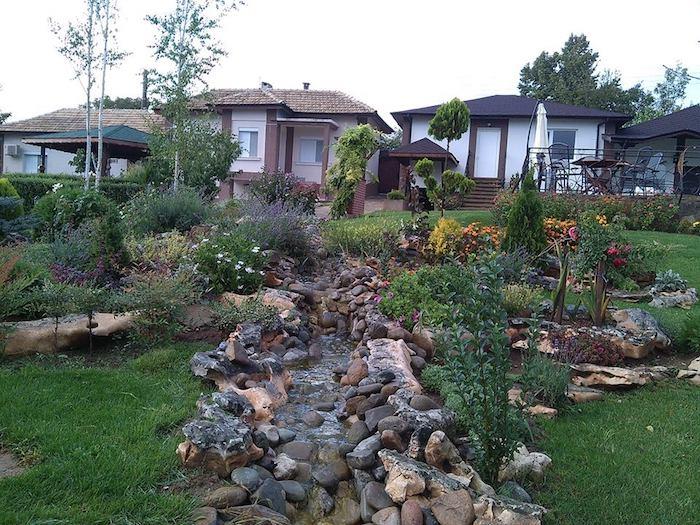 einen gartenteich anlegen, drei häuser und ein steingarten mit grünem rasen und vielen kleinen braunen steinen, gelben und violetten blumen und weißen birken