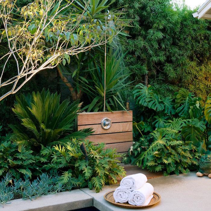 garten mit vielen grünen pflanzen mit grünen blättern und eine gartendusche holz und drei kleine weiße tücher, eine gartendusche bauen ideen