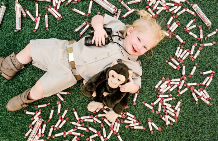 ein süßes kleines Mädchen mit Gorilla Spielzeug, mit Fernglas, Halloween Verkleidung wie kleine Forscherin