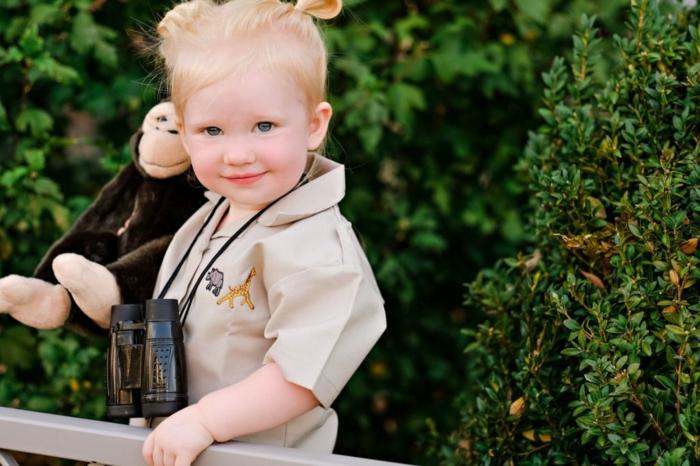 eine kleine Forschrin mit Fernglas und Gorrilla Kuscheltier, Halloween Verkleidung für kleines Mädchen