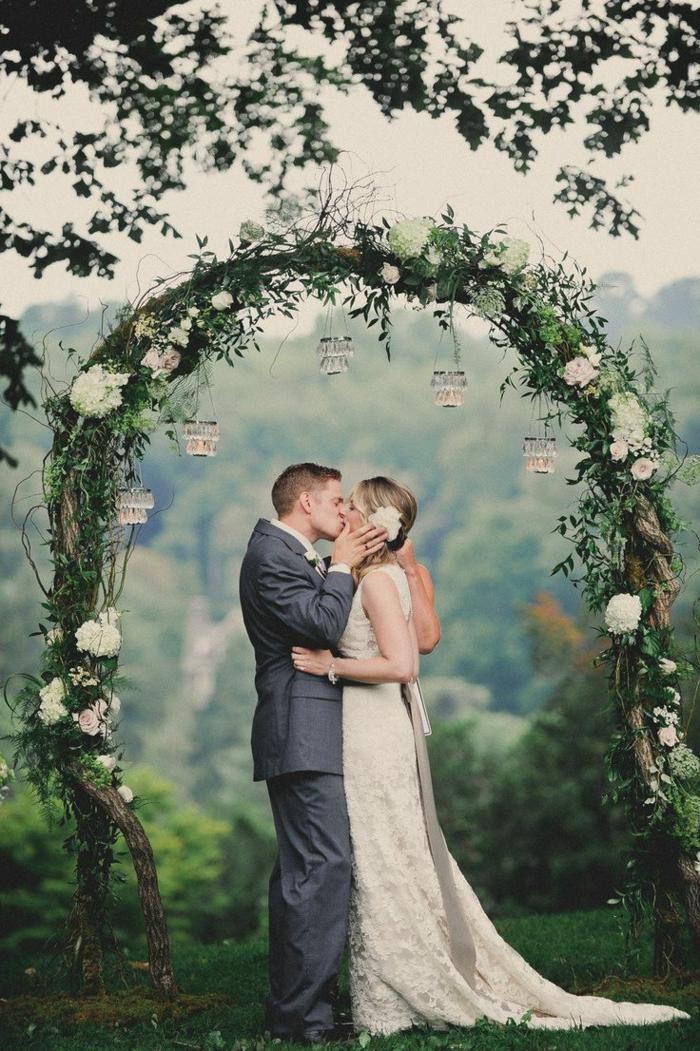 eine schöne Hochzeit von verliebten Brautpaar, ein Bogen aus weißen Blumen, DIY Windlichter, Hochzeitsfeier Ideen