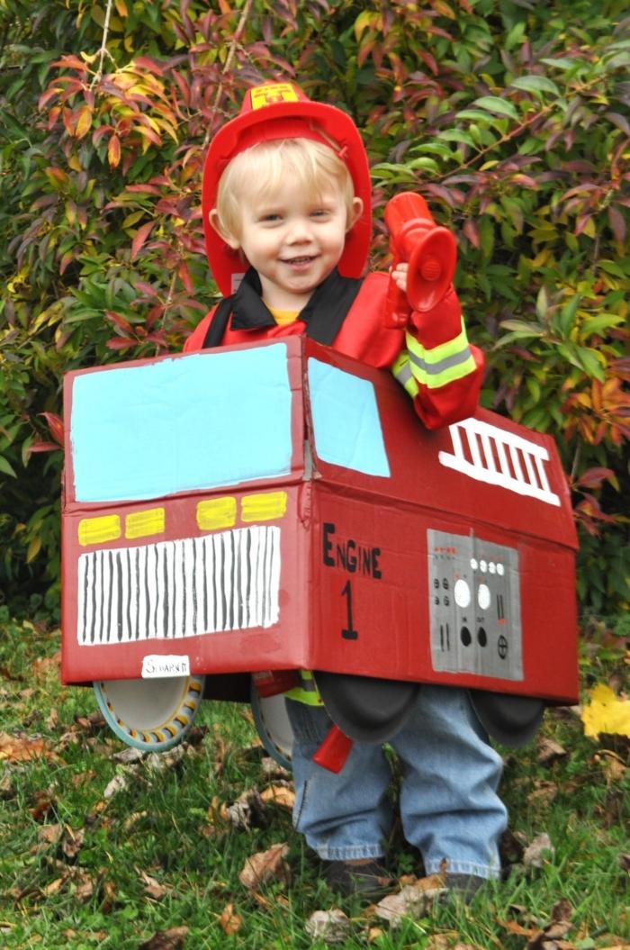 ein kleiner Feuerwehrmann mit seinem Feuerwehrwagen aus Karton, Hut von Feuerwehrmann