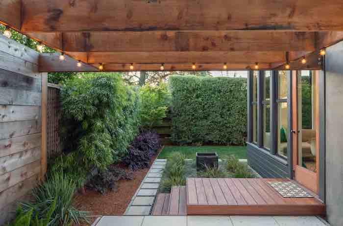 haus mit einer terrasse aus holz, ein garten mit einem sichtschutz aus vielen grünen kletterpflanzen, ein zaun mit sichtschutz pflanzen
