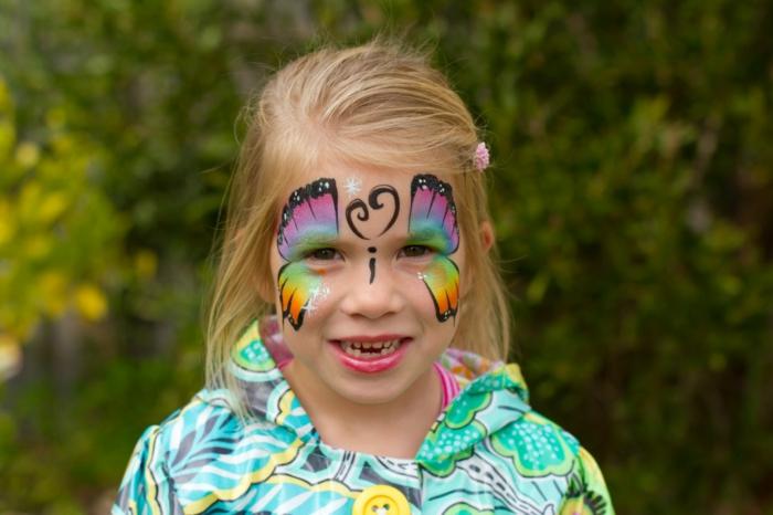 ein blondes Mädchen mit einem bunten Schmetterling, Halloween Schminkideen