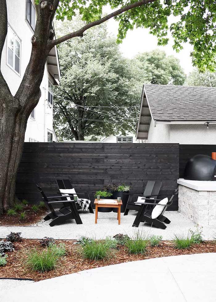 gartengestaltung ideen, ein weißes haus aus holz und mit einem garten mit einem schwarzen zaun aus holz und schwarzengartenmöbeln, stühle und tisch aus holz, sichtschutz holz