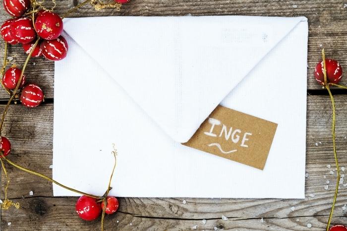Hochzeitsfeier Ideen, weißer Briefumschlag mit einem braunen Anhänger mit Namen