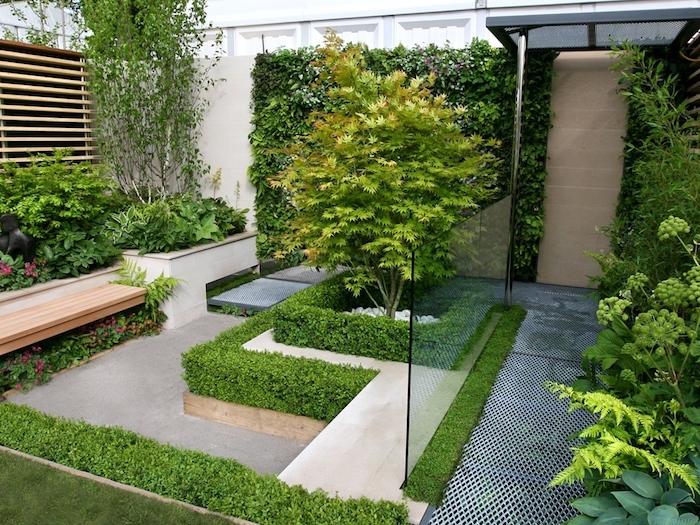 gartenweg und eine hecke mit grünen blätrtern und bäume, eine braune bank aus holz, ein zaun aus holz und sichtschutz pflanzen