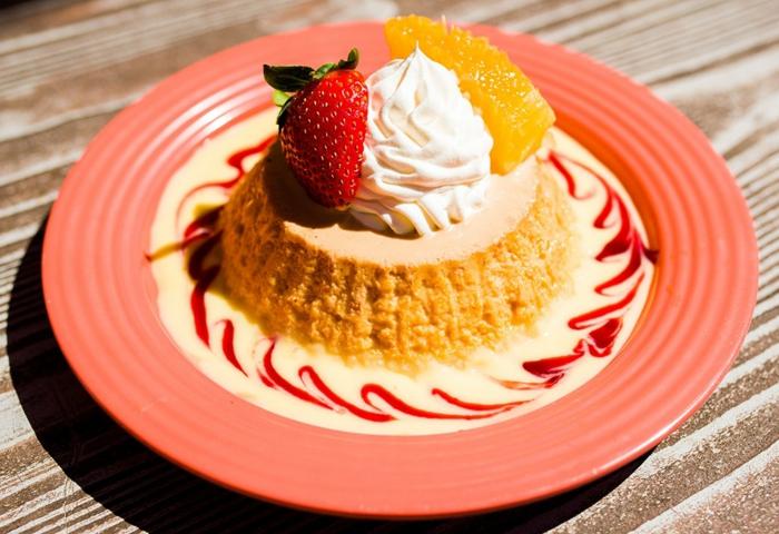 Halloween Rezepte für Torte wie Vulkan, Erdbeere Topping, weiße Creme, eine halbe Erdbeere und Stück Orange als Verzierung
