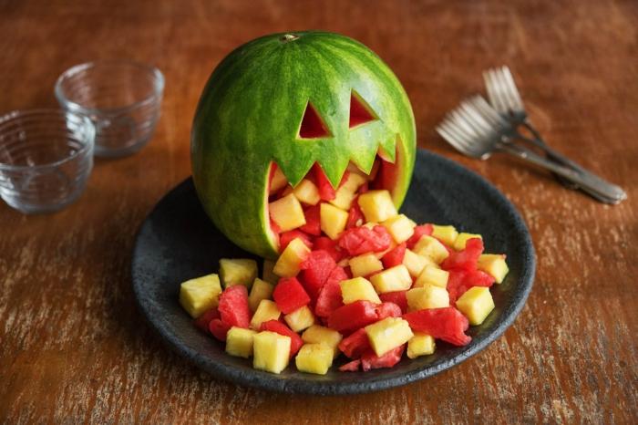 eine Wassermelone, die Melone und Ananasstücke kotzt, Halloween Rezepte für gruselige Stimmung