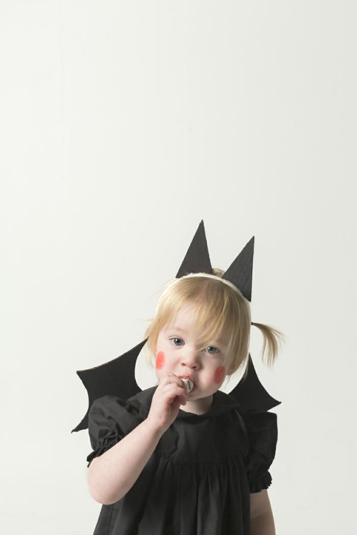 ein kleines Mädchen mit Fledermauskostüm, schnelles Halloween Kostüm, Schminke von roten Wangen