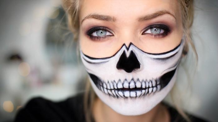 einfaches halloween make up, frau mit blonden haaren, halber totenkopf schminken, blaue augen